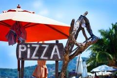En annonserande teckenpizza på stranden arkivfoto