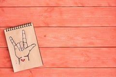 En anteckningsbok av Kraft papper med ett målat språk för amerikanskt tecken för symbolASL ILY älskar jag dig som ligger på det t royaltyfri foto