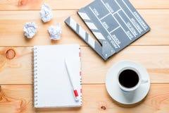 En anteckningsbok, en kopp kaffe och en clapper för att skjuta filmepi Royaltyfri Foto