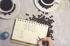 En anteckningsbok med inskriften för 2018 mål med två kaffekoppar Royaltyfri Foto