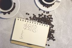 En anteckningsbok med inskriften för 2018 mål med två kaffekoppar Fotografering för Bildbyråer