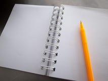 En anteckningsbok och en gul penna Fotografering för Bildbyråer
