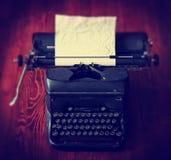 En antik skrivmaskin på en trätabell tonade med en retro vint Royaltyfria Foton