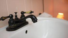 En antik vattenkran lämnas på i ett badrum och dryper in i vask arkivfilmer