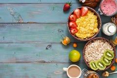 En användbar frukost med sädesslag och mjölkar på blått-gräsplan en lantlig bakgrund Havreflingor, mysli, jordgubbar, kiwi, muttr fotografering för bildbyråer