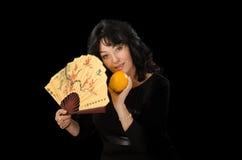 En apelsin för kvinnahanduppehällen och en annan en fan Arkivbild
