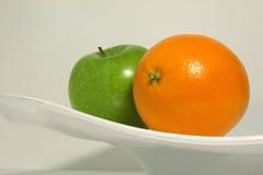 En apelsin och ett äpple Arkivfoto