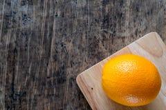 En apelsin på wood texturbakgrund med utrymme för text Organisk frukt Arkivfoto
