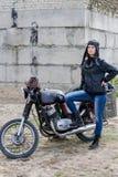 En apokalyptisk kvinna för stolpe nära motorcykeln nära den förstörda byggnaden royaltyfri foto