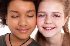 En appelant aux enfants impeccables reliant des joues et montrer leurs visages photographie stock