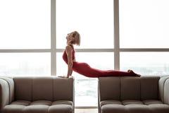 En appeler à la femme forte dans l'équipement rouge lumineux exécutant le yoga photos stock