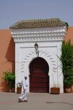 En arabisk man kör framme av en välvd dörr av den Marrakesh moskén Royaltyfri Fotografi