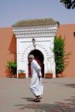 En arabisk man kör framme av en välvd dörr av den Marrakesh moskén Arkivbilder