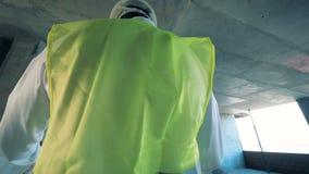 En arbetare, den yrkesmässiga byggmästaren i likformig står i en byggnad, steadicamskott lager videofilmer
