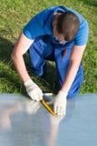 En arbetare gör mätningar av en plast- genomskinlig beläggning för att reparera ett växthus efter en naturkatastrof arkivfoton