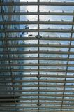 En arbetare gör ren det glass taket av en köpcentrum i Mexico Ci royaltyfri fotografi