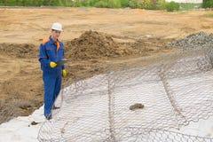 En arbetare i en blå likformig och en vit hjälm, med en minnestavla i hans händer, kontrollerar konstruktionen av kusten royaltyfri foto