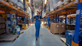 En arbetare i en likformig promenerar en lagerkorridor lager videofilmer