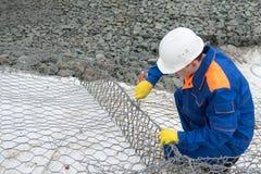 En arbetare i en hjälm på en konstruktionsplats sticker ett fundament från en tråd royaltyfri foto