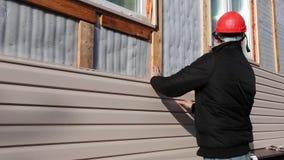 En arbetare installerar den beigea sidingen för paneler på fasaden arkivfilmer