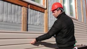 En arbetare installerar den beigea sidingen för paneler på fasaden stock video