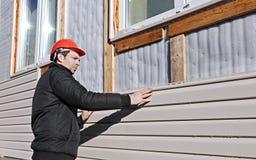 En arbetare installerar den beigea sidingen för paneler på fasaden Arkivfoto