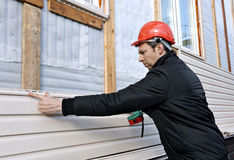 En arbetare installerar den beigea sidingen för paneler på fasaden Royaltyfria Bilder