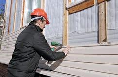 En arbetare installerar den beigea sidingen för paneler på fasaden Royaltyfri Bild