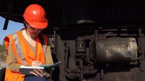 En arbetare kontrollerar av det hydrauliska systemet av en karriärgrävskopa stock video