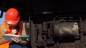 En arbetare kontrollerar av det hydrauliska systemet av en karriärgrävskopa arkivfilmer