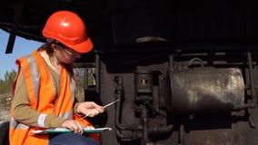 En arbetare kontrollerar av det hydrauliska systemet av en karriärgrävskopa lager videofilmer