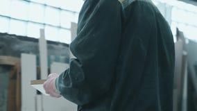 En arbetare med exponeringsglas sågar material i produktion och blickar på resultatet lager videofilmer
