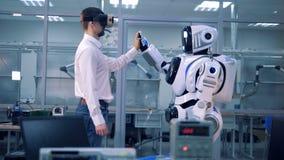 En arbetare och en robot hälsar sig stock video