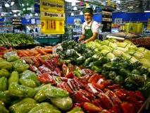 En arbetare ordnar nya frukter och grönsaker på en hylla på en livsmedelsbutik i den Antipolo staden Royaltyfri Bild