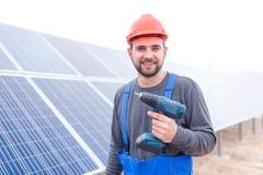 En arbetare på en sol- station är le och rymma en drillborr utomhus Royaltyfri Bild