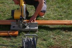 En arbetare såg att trä med en kotlett såg royaltyfri foto