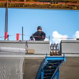 En arbetare ser det sista mellanrummet av bron royaltyfri bild