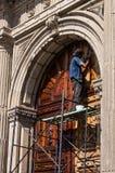 En arbetare som återställer en jätte- dörr Arkivbilder