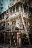 En arbetare som bygger ett bambumaterial till byggnadsställning i Hong Kong, porslin Arkivbilder