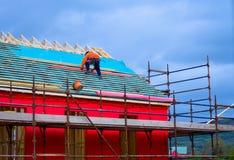 En arbetare som förlägger trä på det sluttade taket av ett nytt hus under konstruktion Royaltyfri Foto