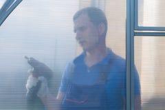 En arbetare som rymmer en skruvmejsel bak den plast- beläggningen av växthuset fotografering för bildbyråer