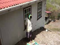 En arbetare som utför underhåll på ett hus i vändkretsarna stock video
