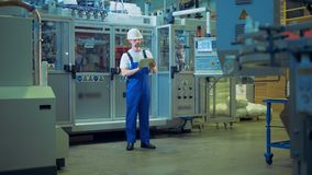 En arbetare står i mitt av en fabriksenhet med en minnestavla lager videofilmer