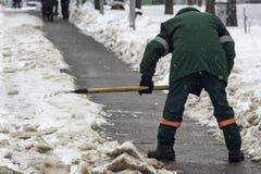 En arbetare tar bort snö från vägen i den kalla vintern royaltyfria bilder