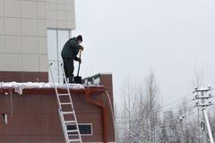 En arbetare tar bort snö och is från taket som gör ren taket som inte uppfyller med arbets- skyddsregler royaltyfri fotografi