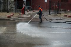 En arbetare tvättar den bitvis gatan var bilar parkeras royaltyfri foto