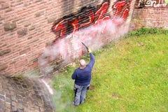 En arbetare tvättar en vägg Arkivbild