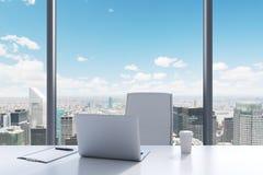 En arbetsplats i ett modernt panorama- kontor med den New York sikten En vit tabell, stol för vitt läder Royaltyfri Foto