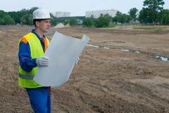 En arkitekt i en vit hjälm som ser en teckning av ett konstruktionsprojekt, på ett öppet område, förberedd jord royaltyfri foto