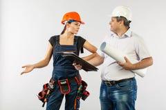 En arkitektman som bär hård en hatt- eller hjälm- och medarbetarebyggmästarekvinna som granskar ritningar arkivfoto